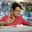 Chinese Man In Computer Shop Checking Bills And Invoices — Stock Photo #71773159