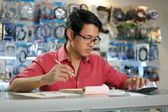 Chinese Man In Computer Shop Checking Bills And Invoices — Stock Photo