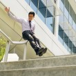 Chinese Businessman Going Downstairs Sliding On Rail For Joy — Stock Photo #75578963