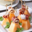 Italian appetizer: melon with ham on skewers vertical — Stock Photo #52111589