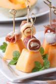 Pieces of melon with ham on skewers close up. Vertical — Stock Photo