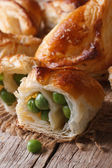 Pies of puff pastry stuffed with green peas macro vertical  — Stock Photo