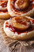 Cakes of flaky pastry with plums close up vertical — Stock Photo