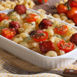Pasta with tomatoes and sausages baked and ingredients — Stock Photo #52648975