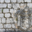 Old stone wall houses with coats of arms — Stock Photo #55588165