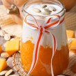 Dessert of pumpkin, cream and seeds in a jar closeup — Stock Photo #56818031