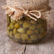 Capers in a glass jar on the old table, close-up — Stock Photo #57899749