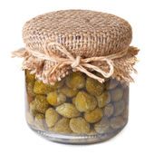 Capers in a glass jar closeup isolated on white background — Stockfoto