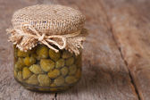 Capers in a glass jar closeup on a wooden. Horizontal — Stockfoto