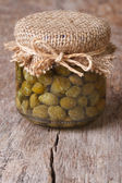 Capers in a glass jar on the old table, close-up — Stockfoto