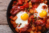 Fried eggs with chorizo in the pan close up. horizontal top view — Stock Photo