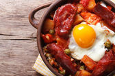 Eggs with chorizo, potatoes and tomatoes in a pot. close up top  — Stock Photo