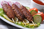 Three kebab of minced meat and fresh vegetables  — Stock Photo