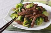 beef with broccoli on a plate close-up and chopsticks. horizont — Stock Photo