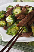 Pieces of beef with broccoli close-up and chopsticks. Vertical — Stock Photo