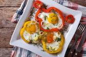 Fried eggs and yellow and red peppers horizontal top view — Stock Photo