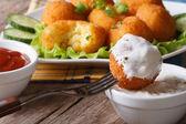 Fried potato balls with sour cream close-up horizontal. — Stock Photo
