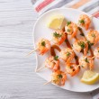 Grilled shrimp on skewers with lemon horizontal top view — Stock Photo #63695643