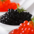 Delicacy black and red caviar macro in white spoons. horizontal — Stock Photo #64684317