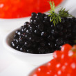 Delicacy black and red caviar macro in white spoons. Vertical — Stock Photo #64684525