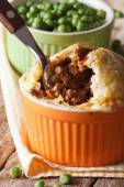 Meat pie in a pot on a background of green pea Vertical  — Stock Photo