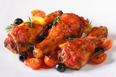 Fried chicken legs in tomato sauce with peppers on a plate — Stock Photo