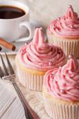 Cupcakes with pink cream and coffee close-up, vertical — Stock Photo