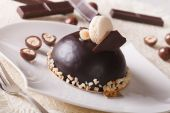 Delicious chocolate cake with nuts, topped with macaroon — Stock Photo