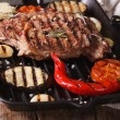 Tasty beef steak with vegetables on a grill pan. horizontal. — Stock Photo #68560781