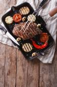 Grilled beef steak with vegetables in pan. Vertical top view — Stock Photo