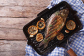 Grilled carp with lemon in a grill pan , horizontal top view — Stock Photo