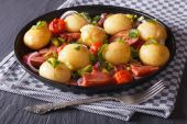 Appetizing new potatoes with fried bacon and herbs on a plate — Stock Photo