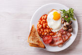 Fried egg with bacon, beans and toast horizontal top view  — Stock Photo