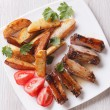 Pork ribs, potatoes and tomatoes on a plate close-up top view — Stock Photo #74355397