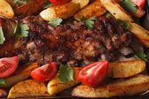 Pork ribs, potatoes and tomatoes macro. horizontal top view — Stock Photo