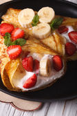 Crepes with strawberries, bananas and cream close-up.  Vertical — Stock Photo