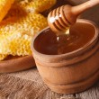 Honey in a wooden bowl and a honeycomb. horizontal, rustic — Stock Photo #78874956