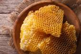Golden honeycombs on a wooden plate. Horizontal top view closeup — Stock Photo