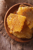 Fresh honeycombs on a wooden plate close-up. vertical top view — Stock Photo