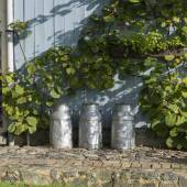 Three churns on a farm — Stock Photo