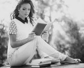 Girl with book in the garden — Stockfoto