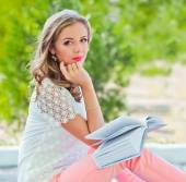 Girl with book in the garden — Stock Photo