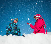 Girl and boy in winter clothes playing with sno — Stockfoto