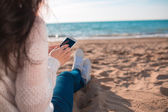 Beautiful girl on the beach with cellphone — Foto de Stock