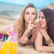 Two girlfriends resting on the beach — Stock Photo #76637961