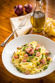 Fettuccine with ham and spring peas — Stock Photo