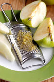 Grated apple with tool stainless — Stock Photo