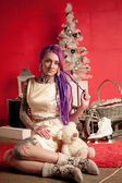 Christmas photo of a girl with purple dreadlocks and tattoos in the studio — Stock Photo