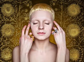 Young androgynous girl with white hair in the studio on yellow  textured background — Stock Photo