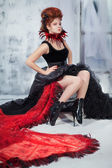 Young beautiful girl in the form of the evil fairy with red hair in a designer dress with a long skirt in unusual shoes and a necklace of feathers — Stock Photo